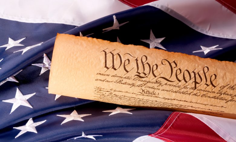 Image of the American Constitution on top of a flag.