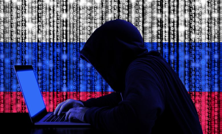 Hacker in a dark hoody sitting in front of a notebook with digital russian flag and binary streams background.