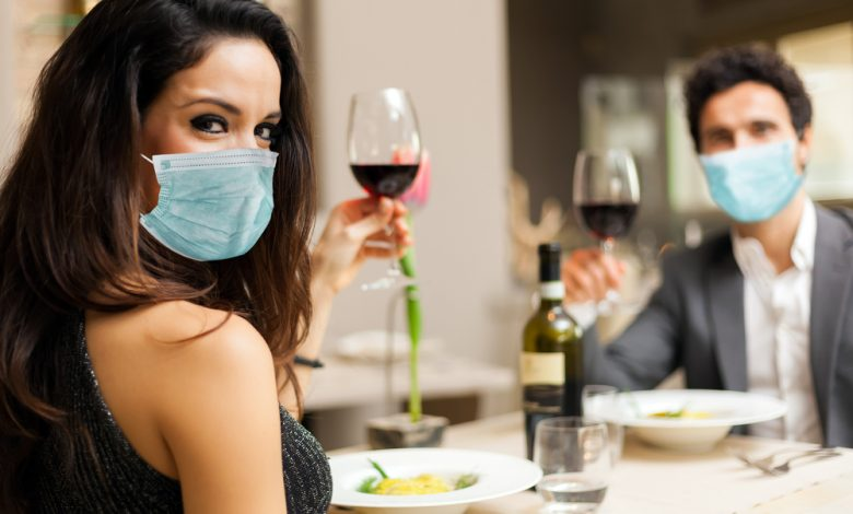 Couple toasting wineglasses in a luxury restaurant and wearing masks.