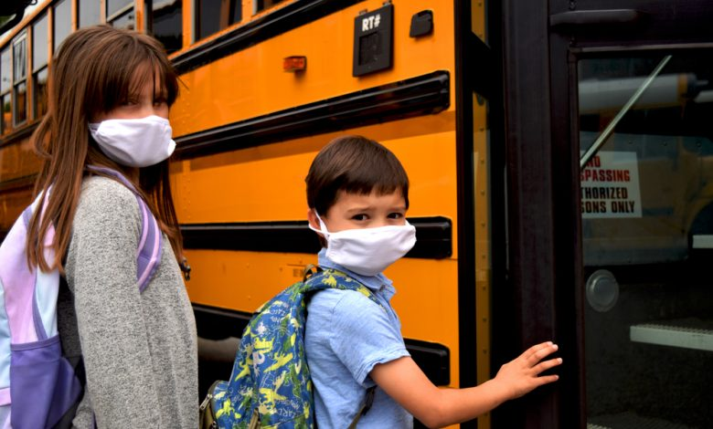 Boy and girl, students, children wearing face masks getting on school bus.