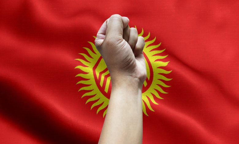 Fist in the air with the flag of Kyrgyzstan on the background