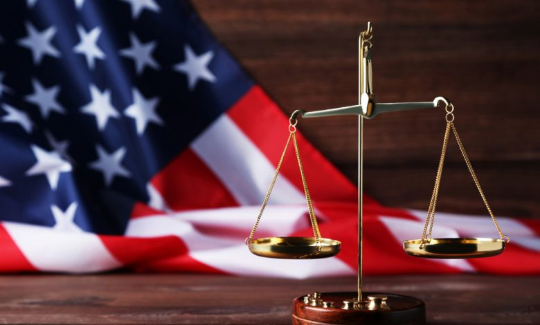 Scales of justice with american flag on brown wooden table.