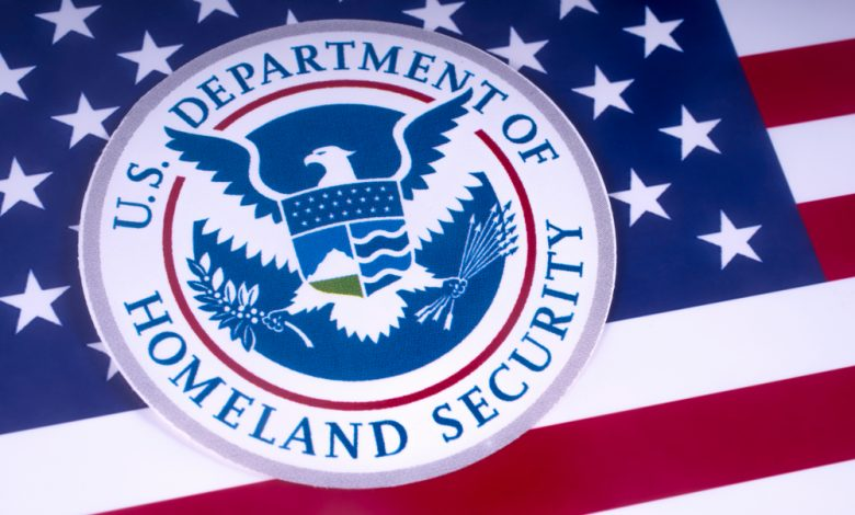 Symbol of the US Department of Homeland Security pictured over the US Flag.