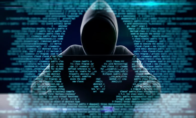 Cyberattack concept image depicting a hacker with code overlay in the shape of a skull