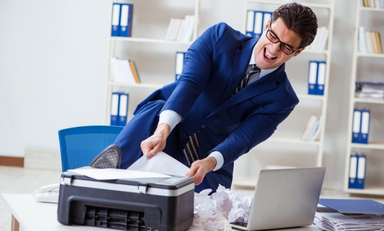 Businessman angry at printer jamming papers.
