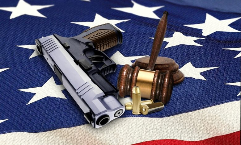 Hand gun with gavel and bullets on ag.merican fla